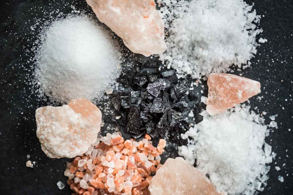 Verschiedene Salze auf schwarzem Stein
